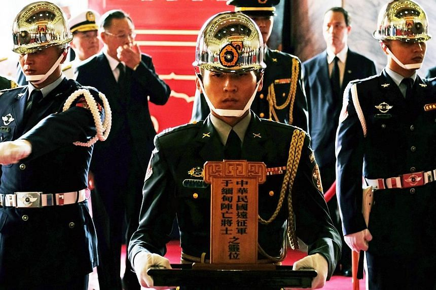 A honor guard (centre) holds a soldiers' tablet during a ceremony to honor the dead soldiers of Taiwan killed in Myanmar during World War II, at the Martyr's Shrine in Taipei on Aug 27, 2014. Taiwan on Wednesday honoured tens of thousands of Kuo