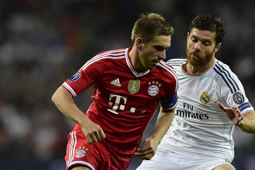 Real Madrid midfielder Xabi Alonso (right) battles Bayern Munich defender Philipp Lahm (left) for the ball during the UEFA Champions League semifinal first leg football match at the Santiago Bernabeu stadium in Madrid on April 23, 2014 . Ge