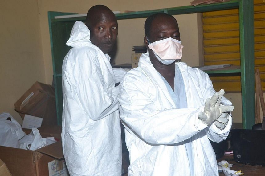 """Health workers take off their protective suits as they finish their shifts at the Pita hospital on Aug 25, 2014.The Ebola outbreak in West Africa has taken 1,552 lives out of 3,069 known cases in four countries and """"continues to accelerate"""", th"""