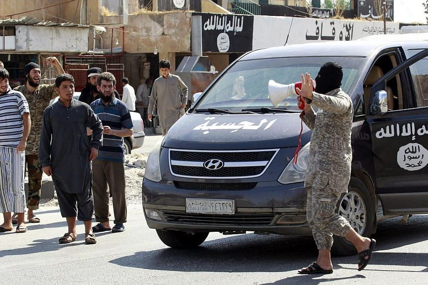 An Islamic State militant uses a loud-hailer to announce to residents of Taqba city, Syria, that Tabqa air base has fallen to Islamic State militants, in nearby Raqqa city on Aug 24, 2014.Police in the Netherlands and Germany have arrested two