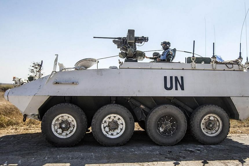 Irish members of the United Nations Disengagement Observer Force (UNDOF) sit on their armoured vehicles in the Israeli-annexed Golan Heights as they wait to cross into the Syrian-controlled territory on Thursday, Aug 28, 2014. A group of 43 Unit
