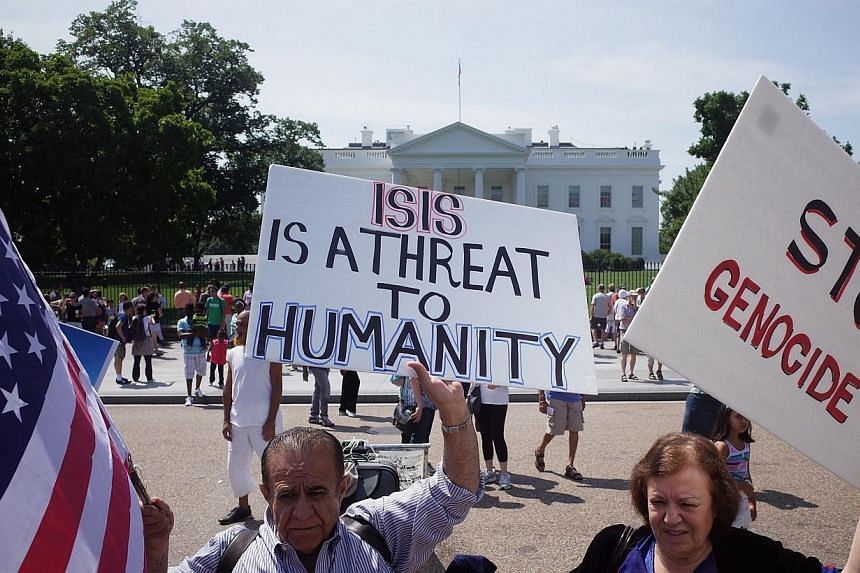 Demonstrators at a rally supporting Kurdistan hold placards protesting against the Islamic State of Iraq and Syria (ISIS) in front of the White House on Aug 16, 2014 in Washington, DC. -- PHOTO: AFP