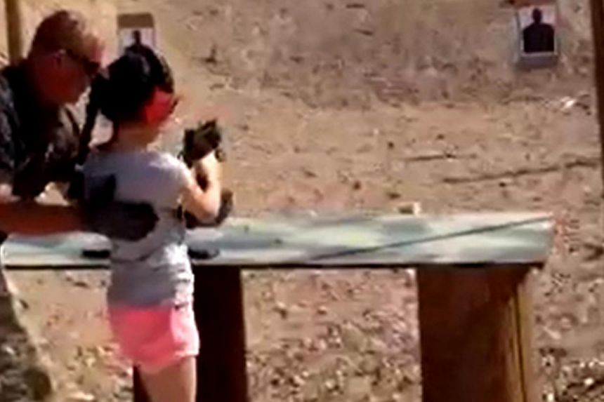 Shooting instructor Charles Vacca stands next to a 9-year-old girl at the Last Stop shooting range in White Hills, Arizona near the Nevada border, on Aug 25, 2014, in this still image taken from video courtesy of the Mohave County Sheriff's Office. T