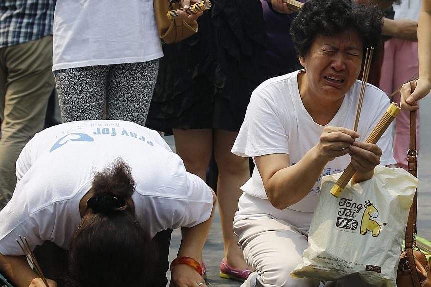 Family members of passengers aboard the missing Malaysia Airlines flight MH370 cry as they burn incense to pray at Yonghegong Lama Temple in Beijing on June 15, 2014. -- PHOTO: REUTERS