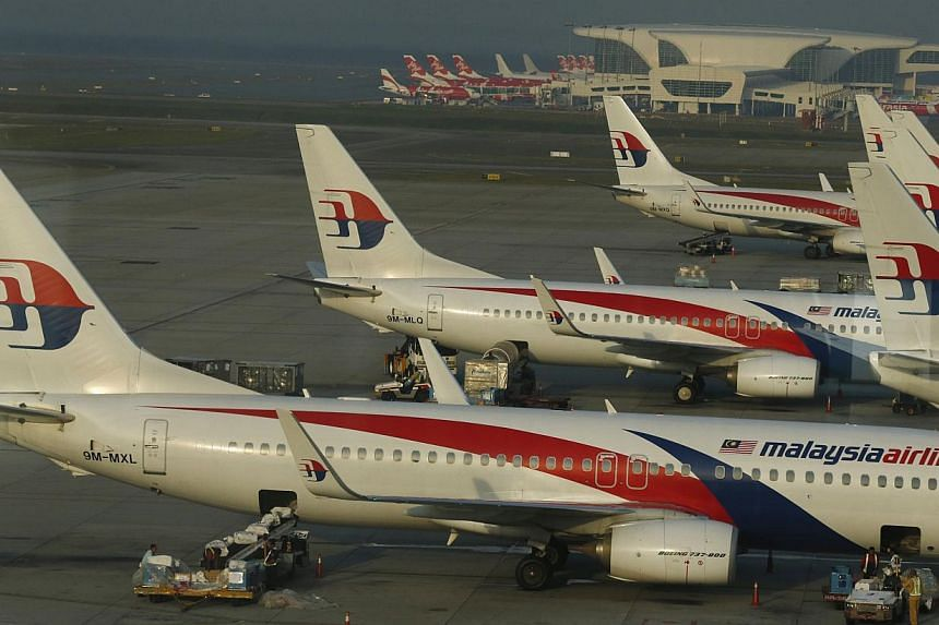 Ground crew work among Malaysia Airlines planes on the runway at Kuala Lumpur International Airport (KLIA) in Sepang on July 25, 2014. Malaysia has signed a memorandum of understanding (MOU) with Australia to strengthen their collaboration in the sea