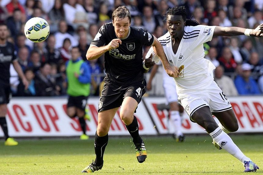 Swansea City's Bafetimbi Gomis (right) challenges Burnley's Michael Duff during their English Premier League match at the Liberty Stadium in Swansea on Aug 23, 2014. -- PHOTO: REUTERS