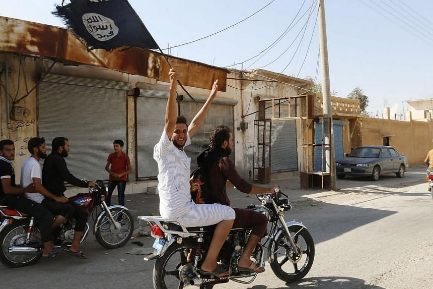 A resident of Tabqa city touring the streets on a motorcycle waves an Islamist flag in celebration after Islamic State militants took over Tabqa air base, in nearby Raqqa city on Aug 24, 2014. -- PHOTO: REUTERS