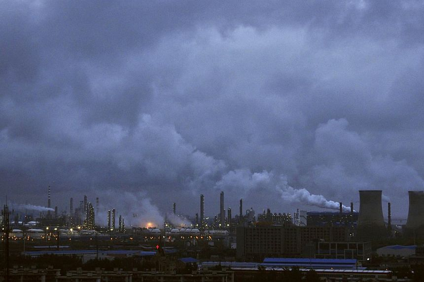 Smoke rises from chimneys and cooling towers of a refinery in Ningbo, Zhejiang province on Aug 19, 2014. -- PHOTO: REUTERS