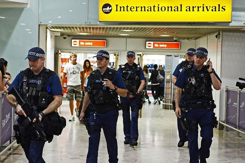 "Armed police officers walk in front of the arrival gate at Heathrow airport, west of London on July 23, 2012. British Home Secretary Theresa May said on Friday the country's terror threat risk level was being raised to ""severe"", meaning an attac"