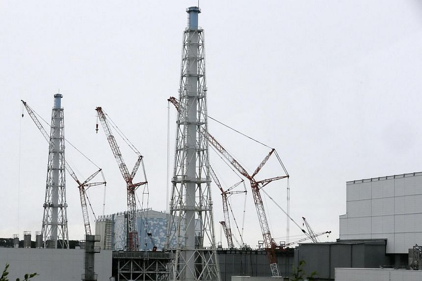 Cranes are seen at the No. 3 reactor building, next to the No.4 building, at Tokyo Electric Power Co.'s (Tepco) tsunami-crippled Fukushima Daiichi nuclear power plant in Fukushima Prefecture on July 9, 2014. A 400kg machine part fell into a nucl