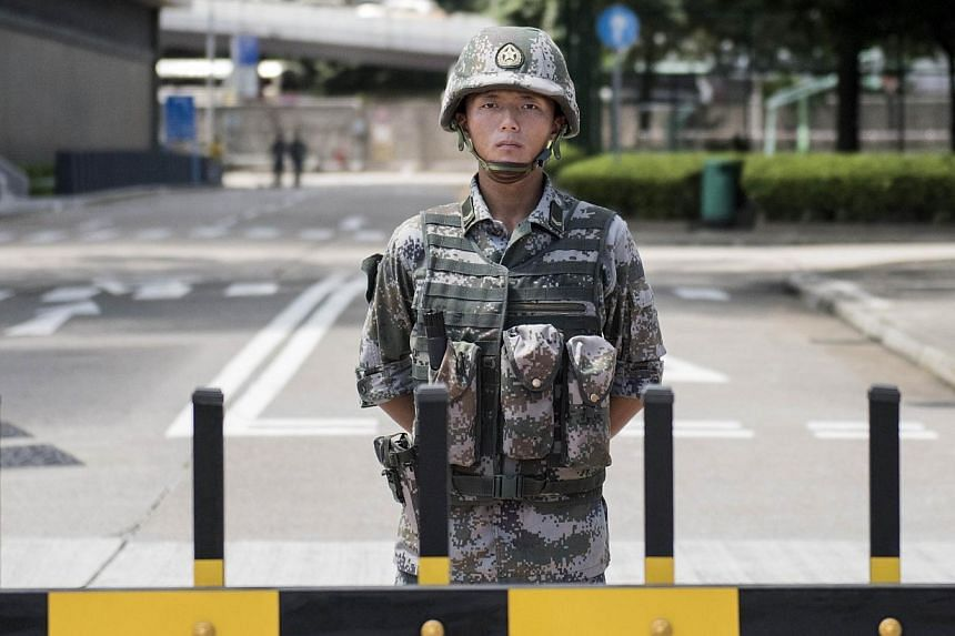 A Chinese People's Liberation Army (PLA) soldier stands guard at the entrance to the PLA's Hong Kong Garrison headquarters in Hong Kong on Aug 29, 2014.Hong Kong democracy advocates expressed alarm on Friday after Chinese army vehicles were pho