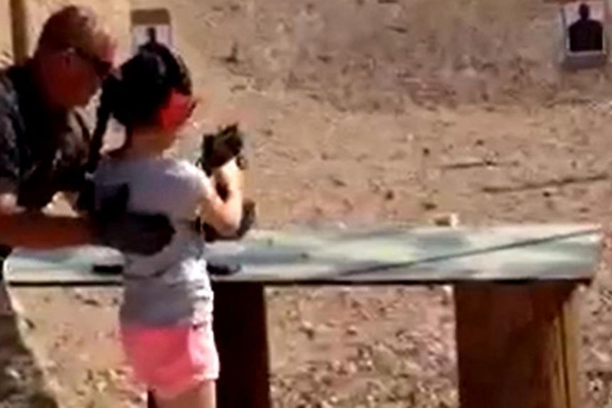 Shooting instructor Charles Vacca stands next to a 9-year-old girl at the Last Stop shooting range in White Hills, Arizona near the Nevada border on Aug 25, 2014, in this still image taken from video courtesy of the Mohave County Sheriff's Office. --