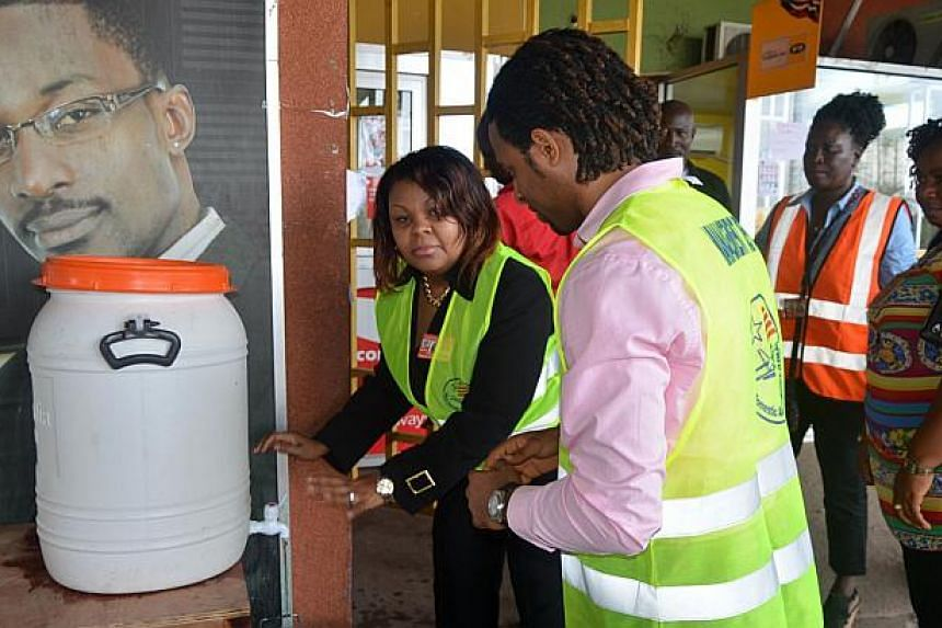 Workers wash their hands in chlorinated water at the Roberts International Airport near Monrovia on August 27, 2014. Ebola-hit nations met for crisis talks on August 28, 2014 as the death toll topped 1,500 and the World Health Organisation warned tha