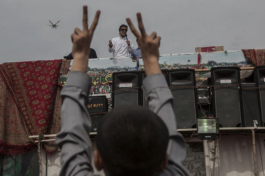 Imran Khan, chairman of the Pakistan Tehreek-e-Insaf political party, addresses supporters while a boy gestures in front of the Parliament house building during the Revolution March in Islamabad on August 28, 2014. He told his supporters that talks t