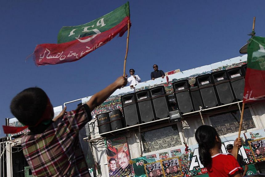 Mr Imran Khan, chairman of the Pakistan Tehreek-e-Insaf (PTI) political party, addresses supporters as children wave PTI's flag, in front of the Parliament building during the Revolution March in Islamabad on August 29, 2014. Former cricketer Imran K