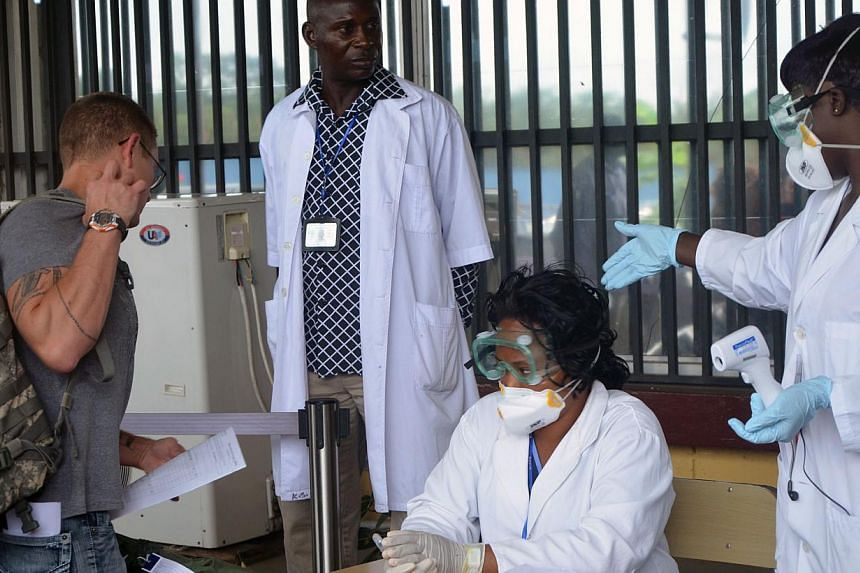 Health agents check a passenger leaving Liberia at the Roberts International Airport near Monrovia on August 27, 2014. Ebola-hit nations met for crisis talks on August 28, 2014 as the death toll topped 1,500 and the World Health Organisation warned t