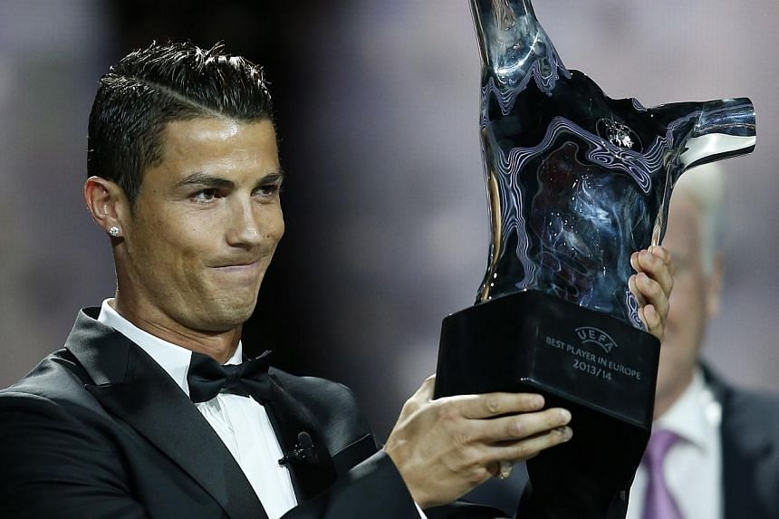 Real Madrid's Portuguese forward Cristiano Ronaldo celebrates holding his UEFA European Player of the Year trophy, on August 28, 2014 in Monaco, after the draw for the 2014/2015 European Champions League group stages. --PHOTO: AFP