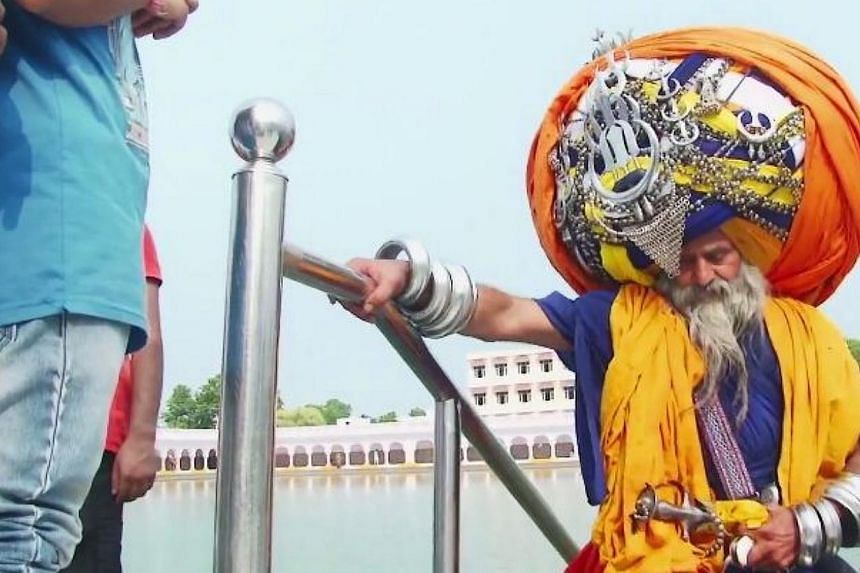 Mr Avtar Singh Mauni, who lives in Punjab, takes six hours to put on his headdress, which stretches to 645m when unwrapped - the length of around six football fields. -- PHOTO: BARCROFT TV/YOUTUBE