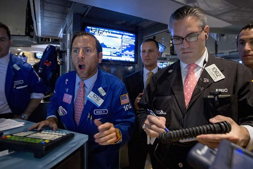 Specialist trader Michael Pistillo (second from left) gives a price for a stock just after the opening bell on the floor of the New York Stock Exchange on August 28, 2014. US stocks fell modestly on Thursday as rising fears about renewed tensions bet