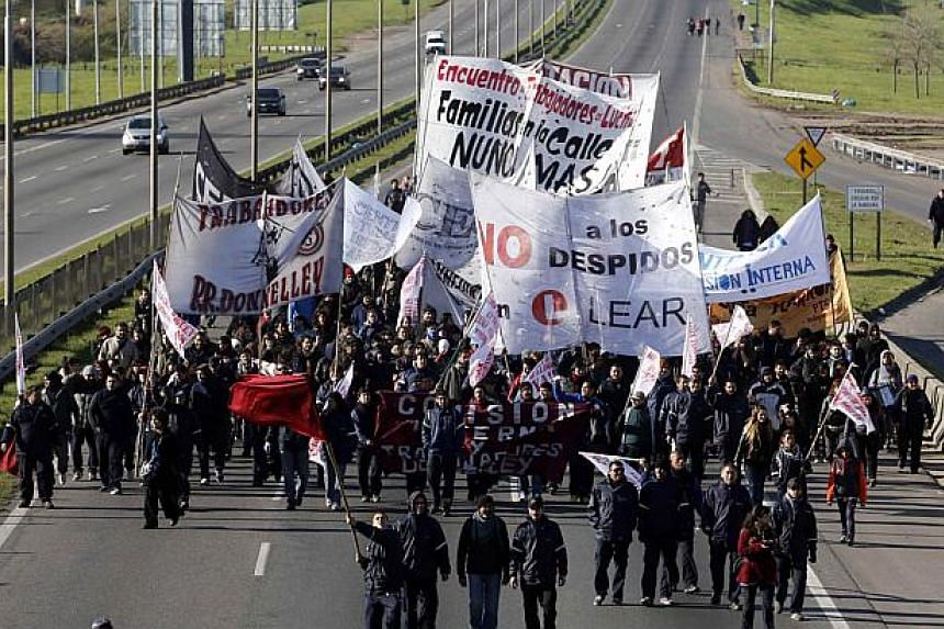 Workers and members of political parties march down a main road as part of a 24-hour strike across Argentina called by opposition labour unions in Buenos Aires on August 28, 2014. The unions staged their second general strike this year on Thursday to
