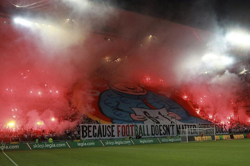 A giant banner of a pig displayed by Legia Warsaw fans is seen amid flares after the Polish club was ejected from the Champions League, during their Europa League play-off match against Kazakhstan's Aktobe in Warsaw on Aug 28, 2014. -- PHOTO: REUTERS