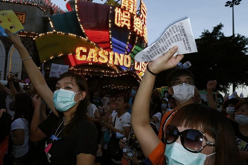 Workers from Macau's six major casinos march past Casino Lisboa during a demonstration in Macau on Aug 25, 2014. Workers are demanding higher wages and for the government to reconsider a policy that would import more foreign workers to the industry.