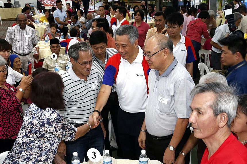 Prime Minister Lee Hsien Loong (centre) mingle with residents, who is also the MP for Ang Mo Kio GRC, presenting pioneer generation packages to pioneers.As Prime Minister Lee Hsien Loong presented Pioneer Generation cards to elderly constituent