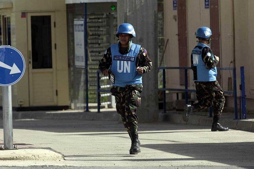 Filipino UN peacekeepers cross the Quneitra checkpoint between Israel and Syria in the Golan Heights on March 9, 2013. Philippine soldiers serving as UN peacekeepers in the Golan Heights clashed with Syrian rebels, Defence Minister Voltaire Gazm