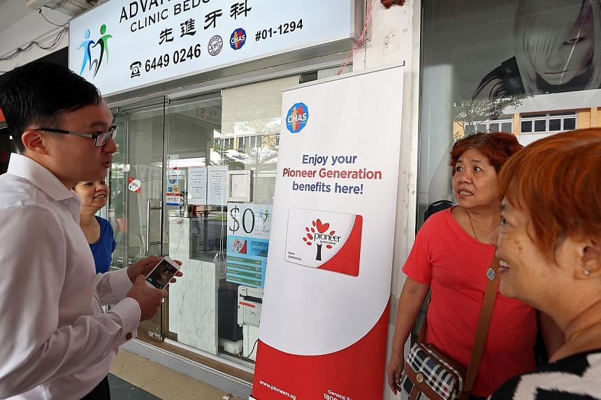 (Left) Dental Surgeon Chua Chew Kiat Simon Jude explains the CHAS scheme to seniors (second from right) Gan Bee Yan, 60, and (right) Ang Ng Tee, 65, on Aug 29, 2014. From Monday, Sept 1, all pioneer generation members will be placed on CHAS, allowing