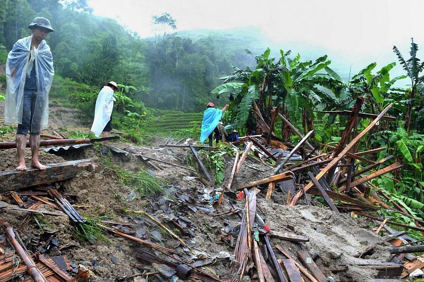 Locals looking at a destroyed house in a village hit by flash floods. Villagers say the weather has become so unpredictable in recent years. -- PHOTO: AGENCE FRANCE-PRESSE