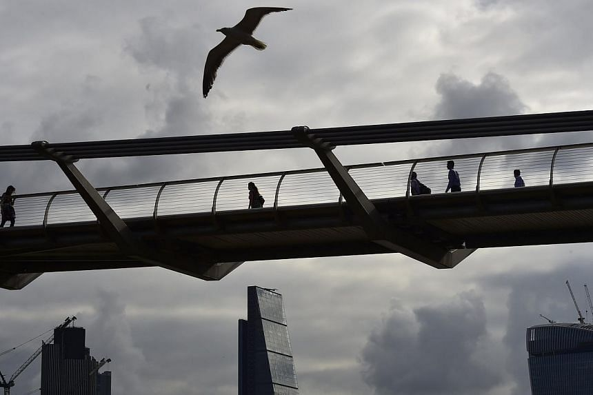 Workers cross the Millenium Bridge with the City of London seen behind, in London on July 30, 2014. Employees in the finance and insurance industry were on average paid a bonus of £13,300 (S$27,500) in the year to April, up 5.5 per cent on a year ea
