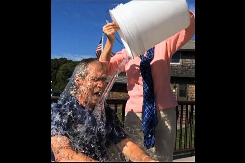 """Former US president George W. Bush taking part in the """"Ice Bucket Challenge"""" in a still image taken from video on August 20, 2014. Bush posted video evidence of his soaking - carried out by wife Laura - on Facebook. -- PHOTO: REUTERS"""