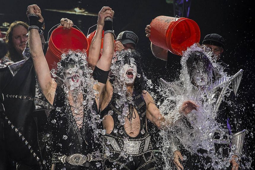 """Eric Singer, Paul Stanley and Tommy Thayer of the band KISS participate in the """"Ice Bucket Challenge"""" at Klipsch Music Centre on August 22, 2014 in Noblesville, Indiana. -- PHOTO: AFP"""