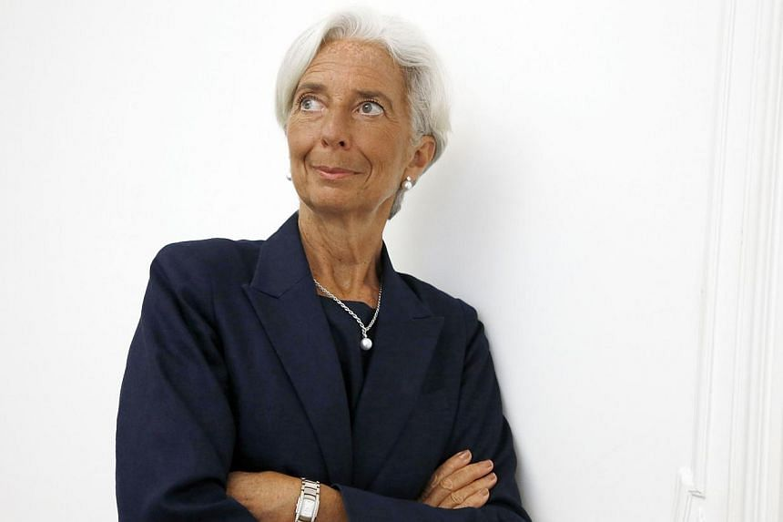 """IMF chief Christine Lagarde poses on the sideline of a press conference on August 27, 2014 at her lawyer's office in Paris, after announcing she had been charged for """"negligence"""" over a multi-million-euro corruption case relating to her time as Frenc"""