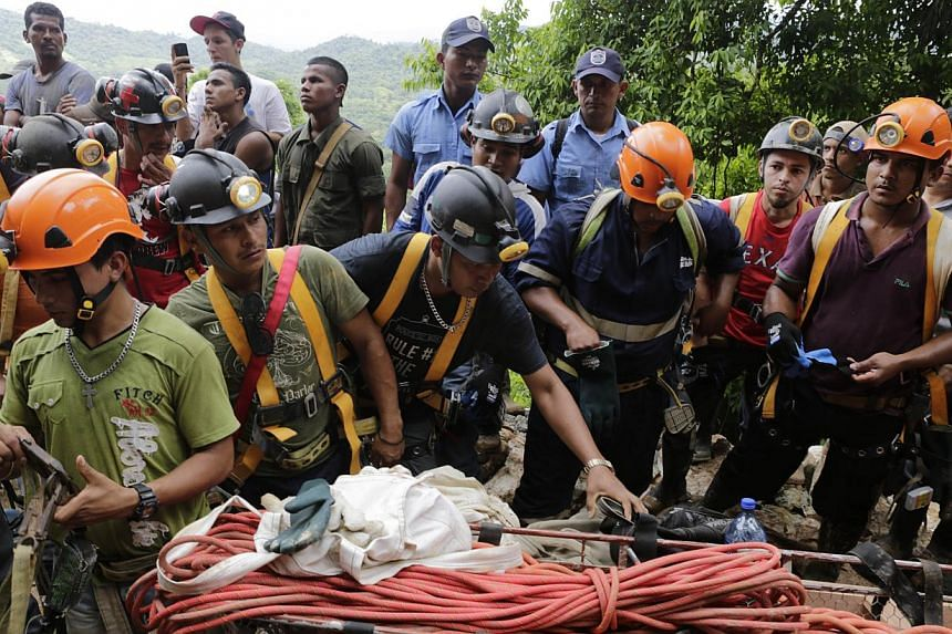 Miners help rescuers in their attempt to reach a group of fellow miners trapped in a gold mine in the community of El Comal, near Bonanza in northeastern Nicaragua, on August 29, 2014. At least 20 miners are trapped alive deep underground after an in