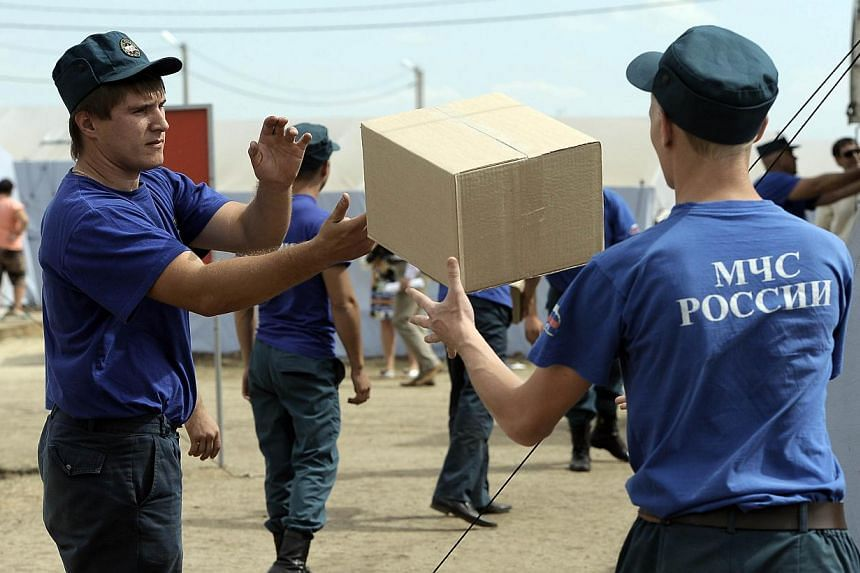 Employees of Russian Emergency Ministry carry boxes with humanitarian aid in a refugee camp for refugees from eastern Ukraine near the Russian city of Donets'k, Rostov region, about 15 kilometres from the Russian-Ukrainian border. -- PHOTO: AFP