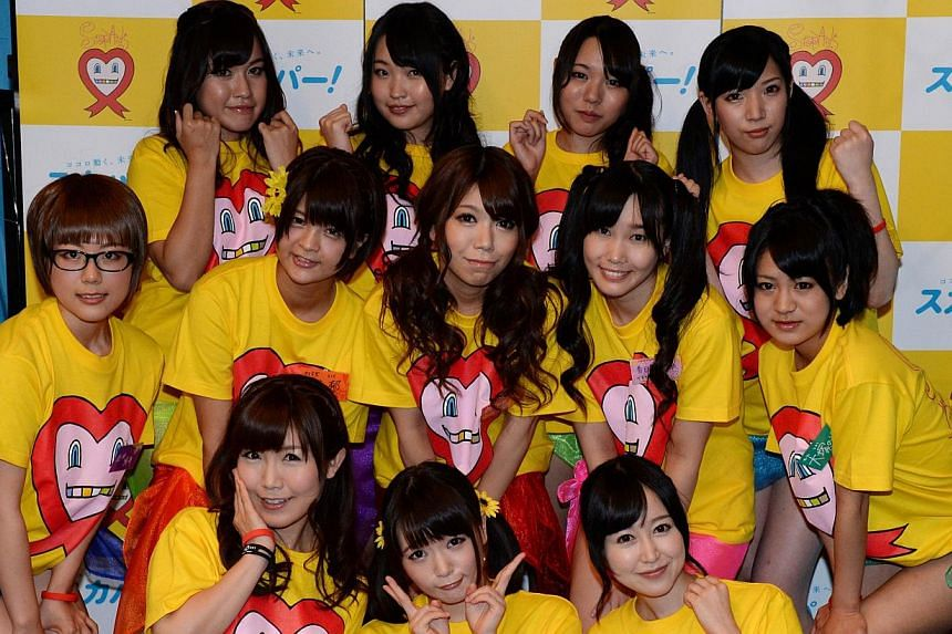 Nine Japanese porn actresses, (middle left-right) Kotone Nishida, Iku Sakuragi, Rina Serino, Yui Kasugano and Nodoka Otsuka, (rear left-right) Yuria Kitahara, Riku Nekota, Yumena Muro and Karin Natsumi, pose with three supporters (front) in Tokyo on