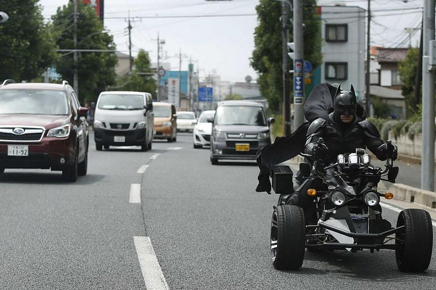 """A 41-year-old man going by the name of Chibatman rides his """"Chibatpod"""" on the road in Chiba, east of Tokyo, Aug 31, 2014.A man who dresses up like the Dark Knight and zips around Chiba sprawled on a three-wheeled motorcycle is setting this east"""