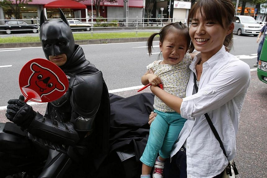 """A woman carrying a crying child poses for pictures next to a 41-year-old man going by the name of Chibatman sitting on his """"Chibatpod"""" in Chiba, east of Tokyo, Aug 31, 2014.A man who dresses up like the Dark Knight and zips around Chiba sprawle"""