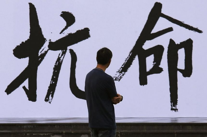 """A pro-democracy activist looks at a backdrop with Chinese characters that read """"disobedience"""", built for an Occupy Central civil disobedience campaign, near the financial Central district in Hong Kong on Aug 31, 2014. The former British colony is poi"""