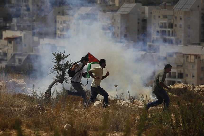 Palestinian protesters and a photographer run from tear gas fired by Israeli soldiers during clashes in the West Bank village of Bilin near Ramallah on Aug 29, 2014. Israel announced plans on Sundaym Aug 31, to expropriate 400ha of Palestinian l