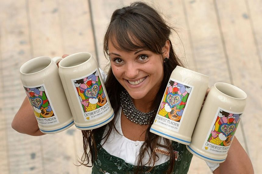 A girl presents the new Oktoberfest beer festival mug in an Oktoberfest tent in Munich, southern Germany, on Aug 21, 2014. Bakers in Bavaria are threatening to go on strike during Germany's famed Oktoberfest over a pay dispute, depriving beer fe