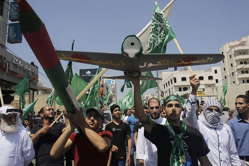 Palestinians hold a mock rocket and a model of a Hamas-made drone during a rally celebrating what they said was a victory by Palestinians in Gaza over Israel, following a ceasefire, in the West Bank city of Hebron on Aug 29, 2014. -- PHOTO: REUTERS
