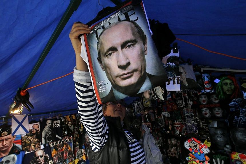 A vendor sells T-shirts printed with images of Russia's President Vladimir Putin at a street store in the center of St. Petersburg, on Aug 31, 2014. Russian President Vladimir Putin called on Sunday for immediate talks on the future of war-torn