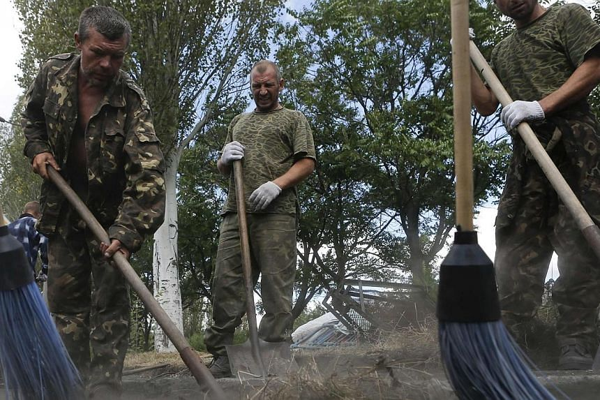 Prisoners-of-war, who are Ukrainian servicemen captured by pro-Russian separatists, clean a street in Snizhne (Snezhnoye), Donetsk region, on Aug 29, 2014.Ukraine has handed over a group of captured Russian paratroops and Russia has returned 63