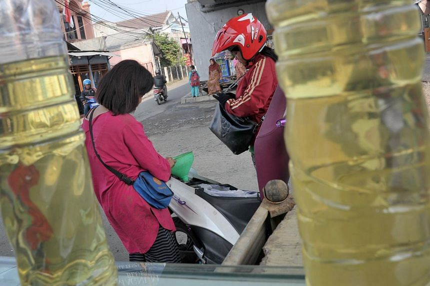 This picture taken on August 29, 2014 shows a motorist (right) filling up her motorcycle with subsidized gasoline at a kiosk in Jakarta. Just weeks before Joko Widodo takes office in Indonesia, a ham-fisted attempt by the outgoing government to tackl