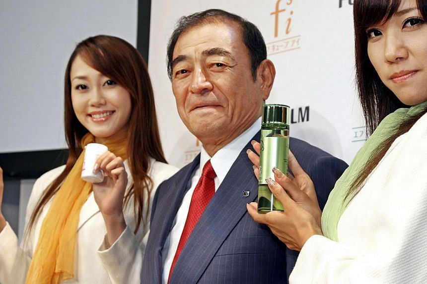 This file picture taken on September 12, 2006 shows Japan's camera giant Fujifilm CEO Shigetaka Komori (center) showing off the company's new three skin care items (R green bottles) and dietary supplements (left) in Tokyo. When Japan announced it was