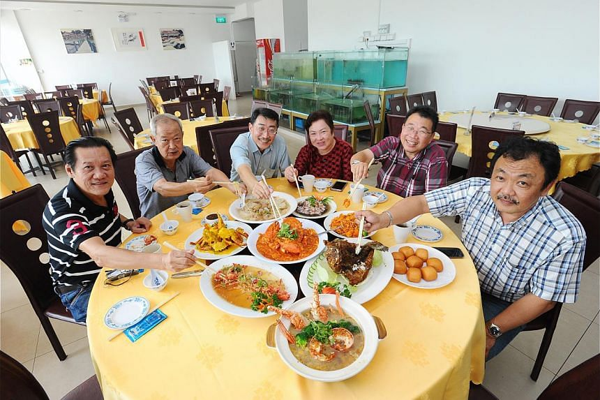Long-time customers (from left) Larry Koh, Ng Jiak Soon, T.K. Ng, Lily Meow, Derrick Meow and Daniel Ng enjoying Ponggol Hock Kee Seafood restaurant's signature dishes.