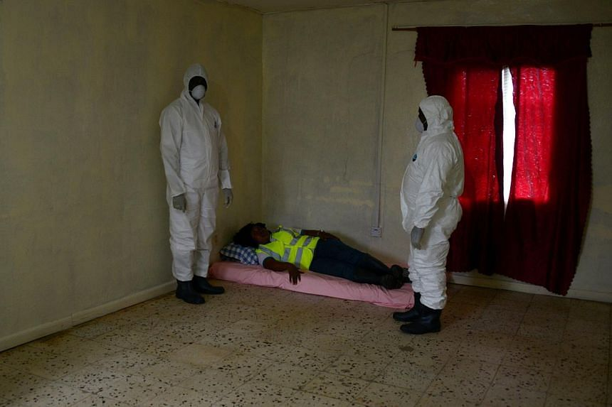 An Ebola prevention drill at a port in Liberia's capital Monrovia. Experts said the outbreak will not end until people calm down and help their infected neighbours instead of fleeing from them.