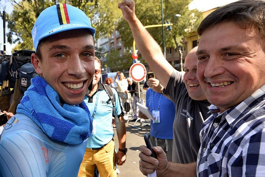 Belgian cycling star Igor Decraene (left) celebrates with his father (right) on September 24, 2013 after winning the men's juniors time trial race at the World Cycling championships in Florence. Belgium cycling lost one of its budding stars on August